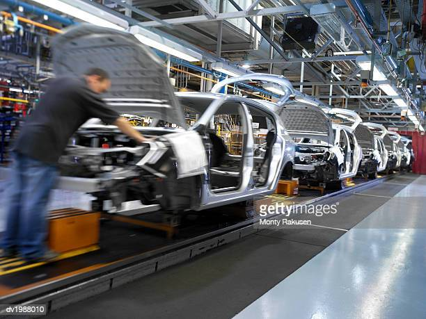 Man Working on a Car Assembly Line in a Factory