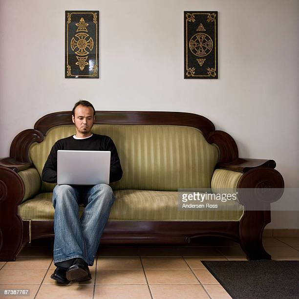 man working on a laptop computer - mid adult men stock pictures, royalty-free photos & images