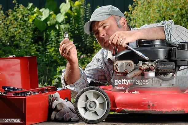 Homme travaillant sur un lawnmower dans le jardin.