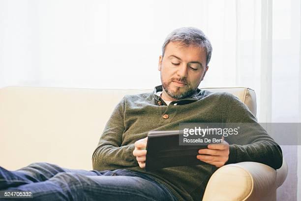 Homme travaillant sur une tablette à la maison