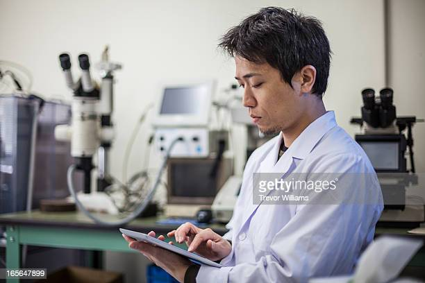 a man working on a tablet computer in a lab - place of research stock pictures, royalty-free photos & images