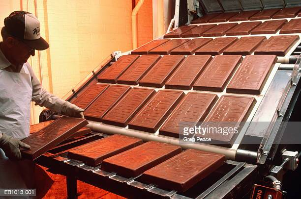 man working on assembly line in chocolate factory - chocolate factory stock photos and pictures