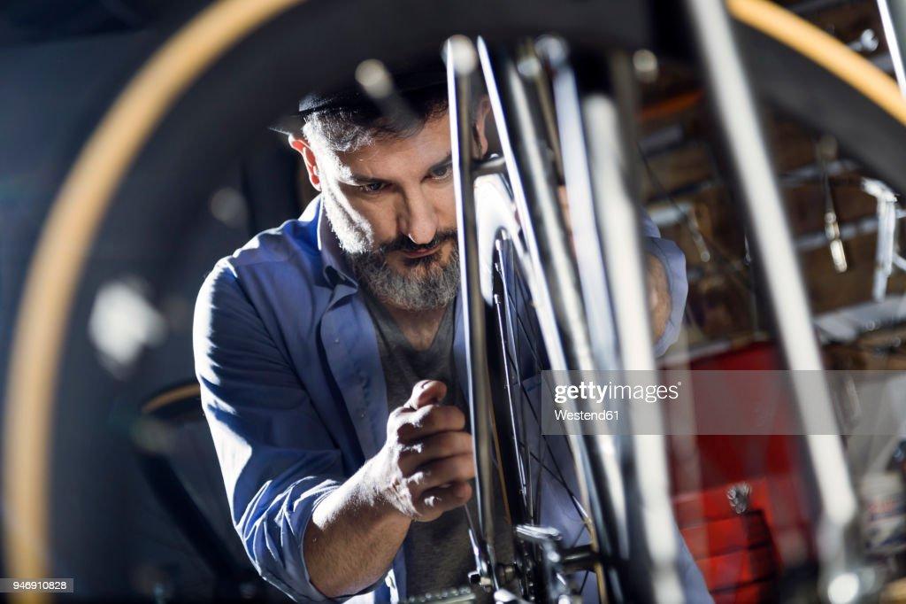 Man working on bicycle in workshop : Stock-Foto
