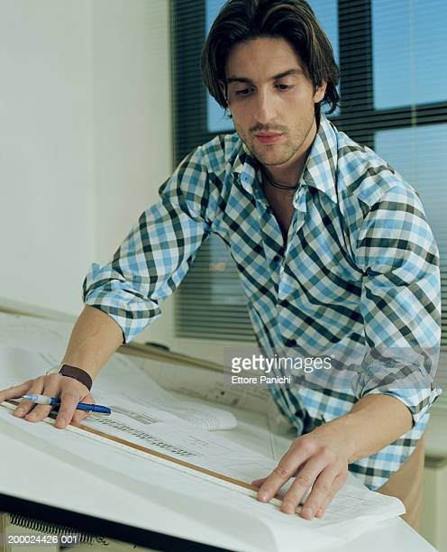 Man working on blue print at drafting table