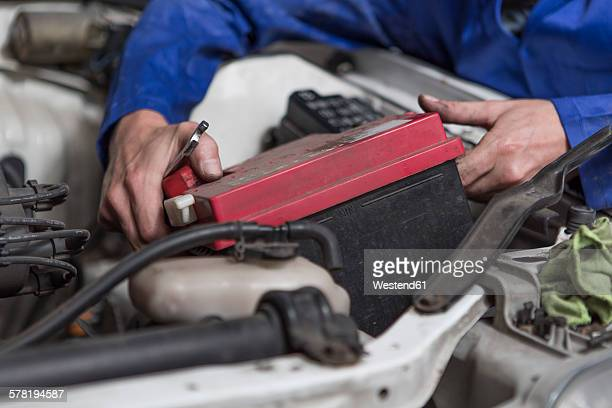 Man working on car removing battery