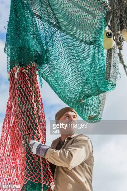 Man working on commercial fishing boat, preparing net