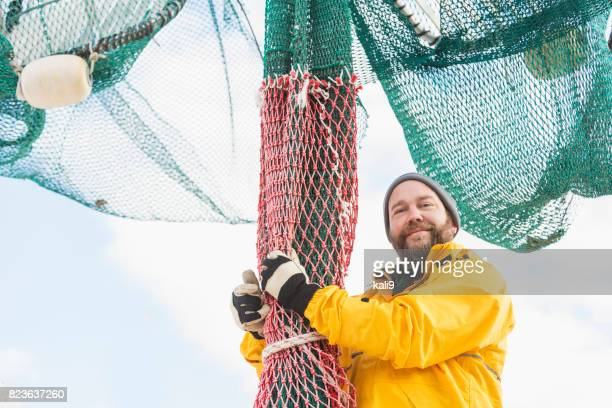 Man working on commercial fishing boat, preparing net