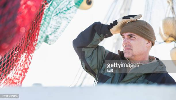 Man working on commercial fishing boat putting on hat