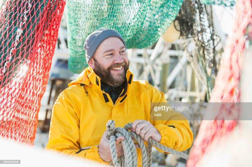 Man working on commercial fishing vessel : Stock Photo