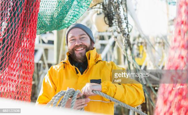 man working on commercial fishing vessel - fishing industry stock pictures, royalty-free photos & images