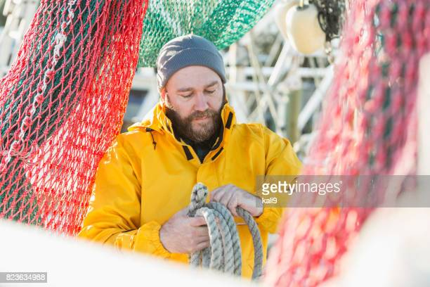 Man working on commercial fishing vessel