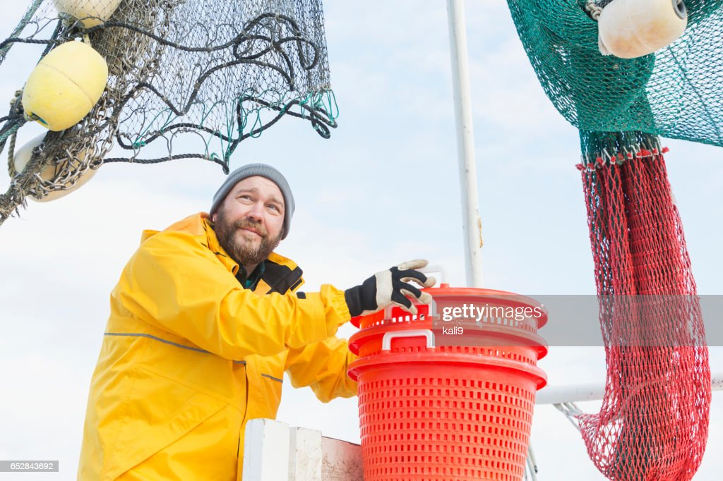 Man working on commercial shrimp boat stacking baskets : Foto stock