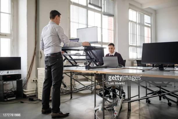 man working on computer at ergonomic standing desk in office - 人間工学 ストックフォトと画像