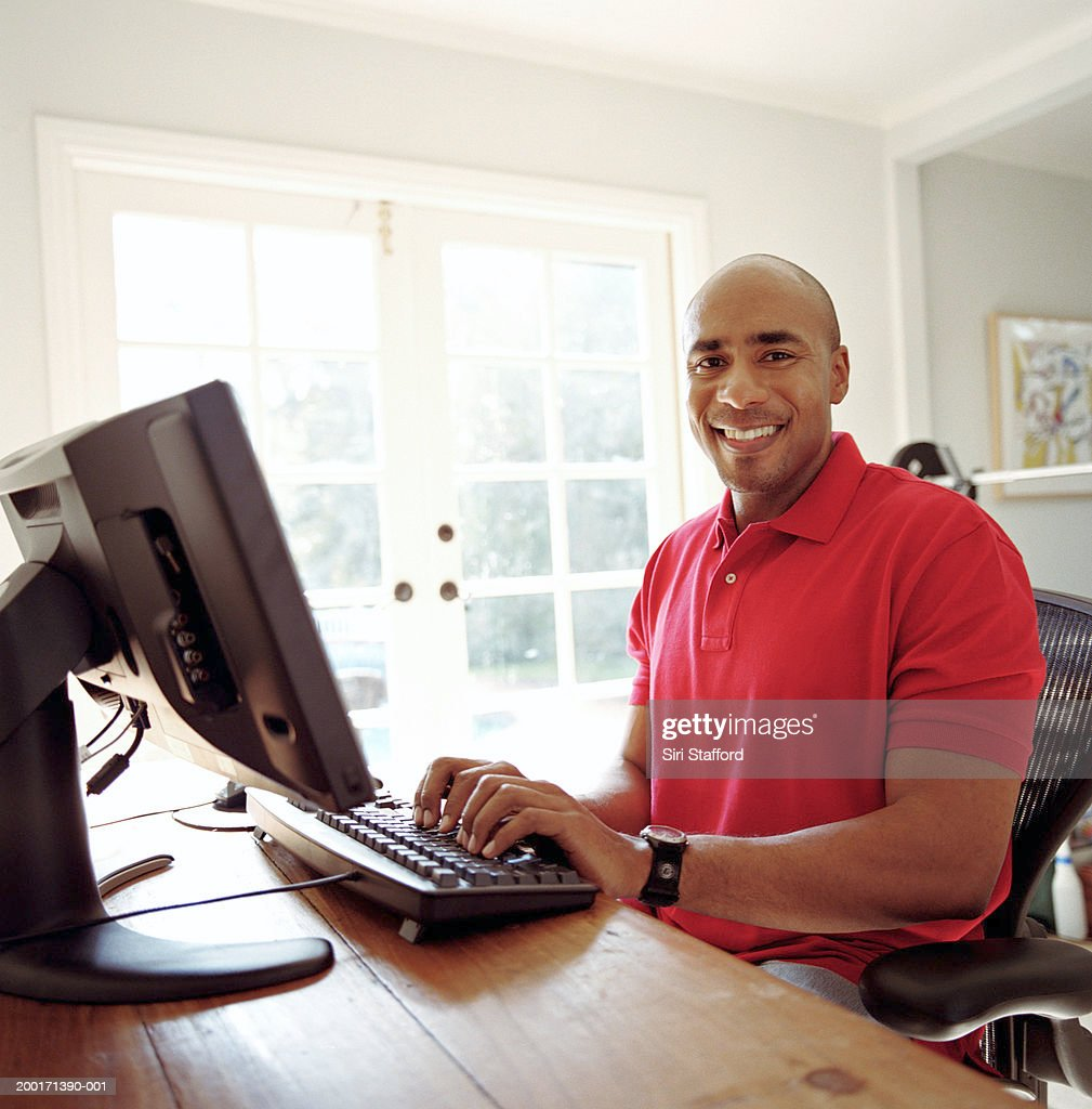 Man working on computer in home office : Stock Photo