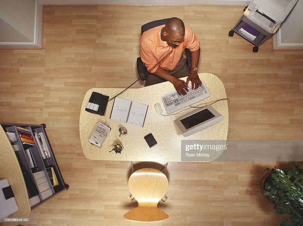 Man working on computer in office, talking on phone overhead view : Stock Photo