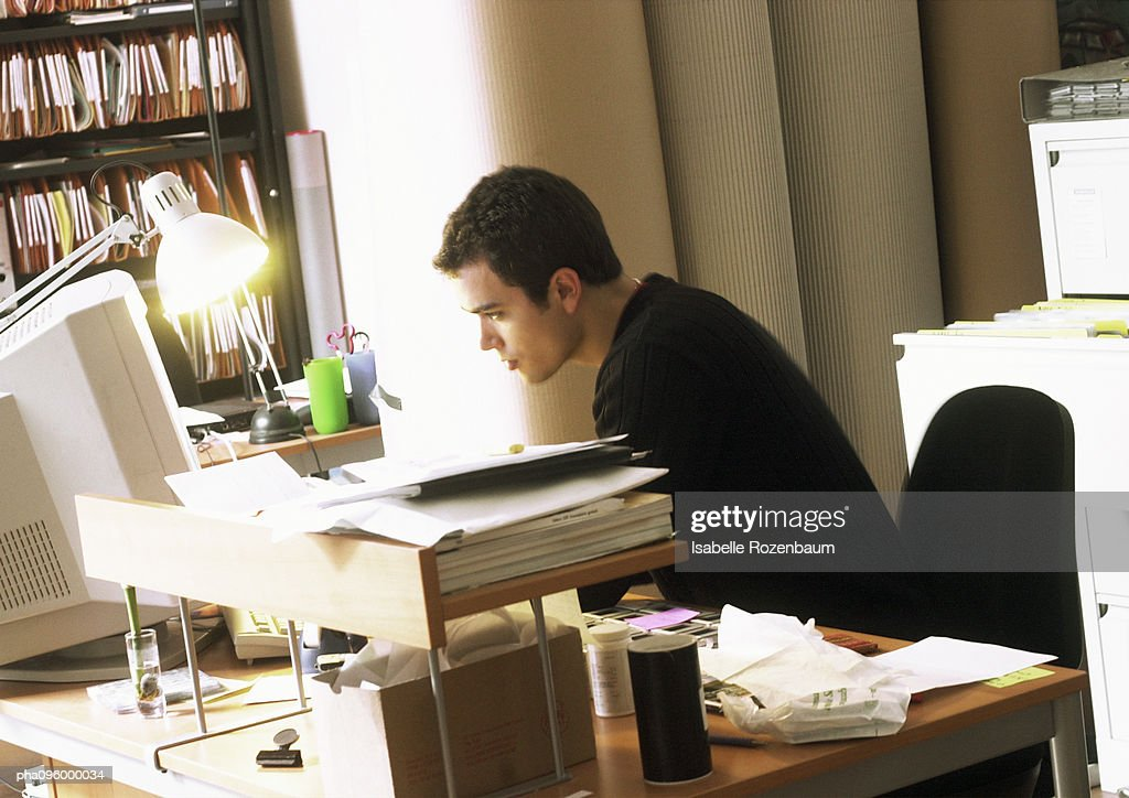 Man working on computer, seen from profile : Stock Photo