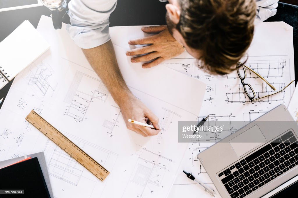 Man working on construction plan at desk, top view : Stock-Foto