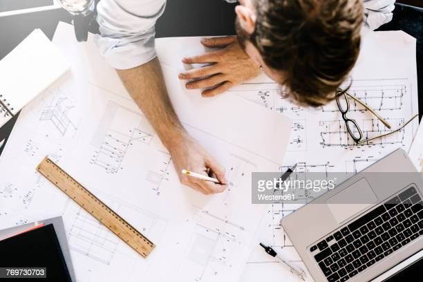 man working on construction plan at desk, top view - skizze stock-fotos und bilder