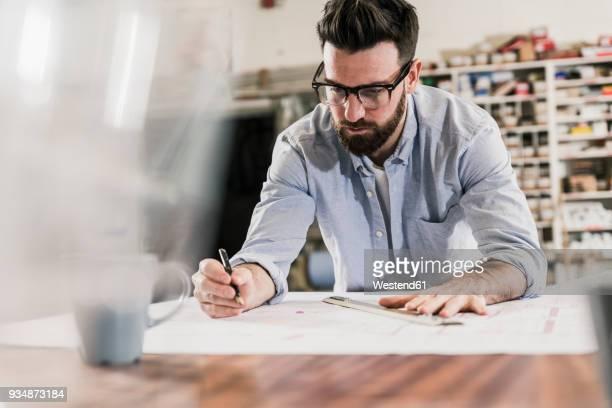 man working on construction plan - designer einrichtung stock-fotos und bilder