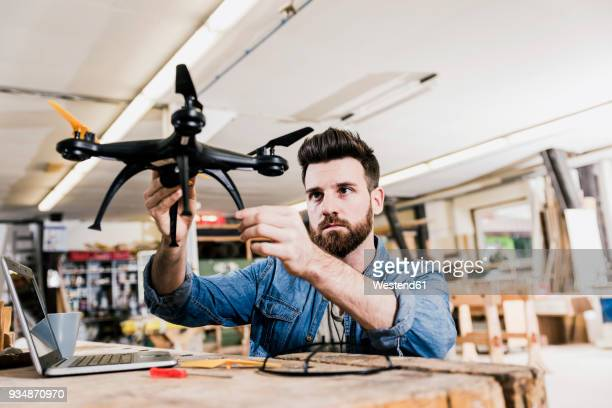 man working on drone in workshop - drone photos et images de collection