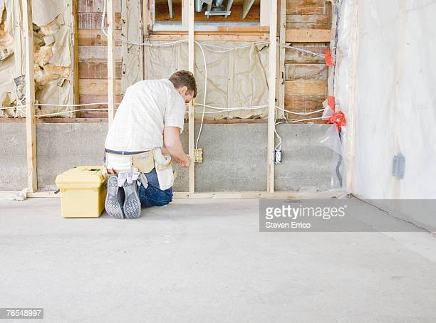 Man working on electricity in house under construction, rear view