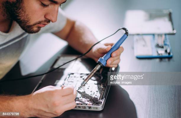 Man working on fixing motherboard of laptop