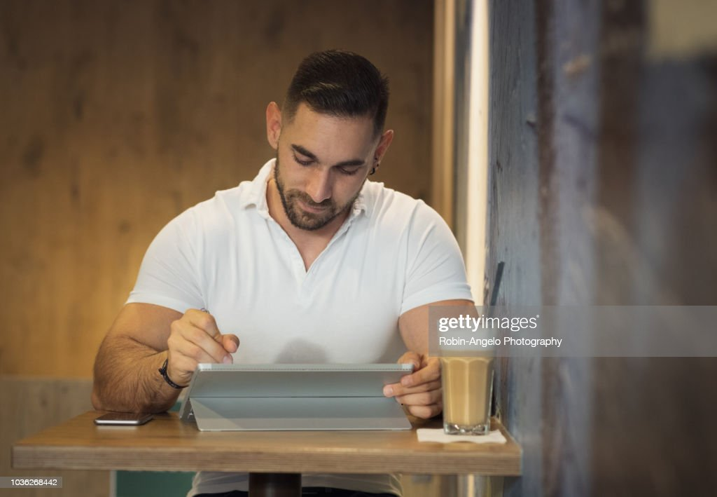 A man working on his laptop in a café : Photo