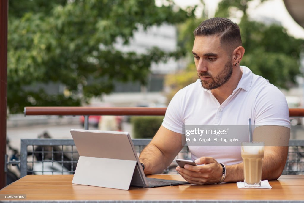 A man working on his laptop in a café : Stock Photo