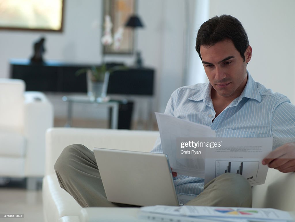 Man working on his laptop while relaxing at home : Stock Photo