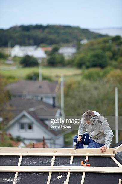 Man working on house roof