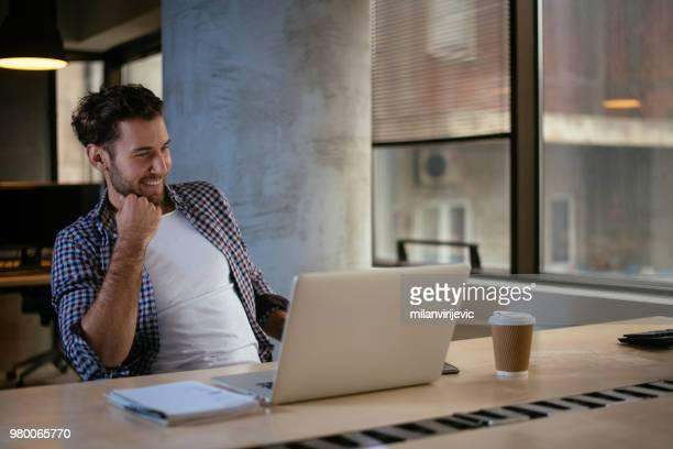man working on lap top in the office - friday stock pictures, royalty-free photos & images