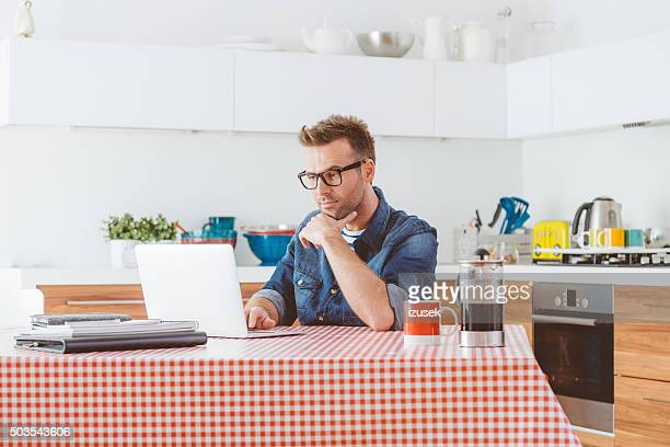 man working on laptop at home in the kitchen - izusek stock photos and pictures