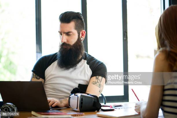 Man working on laptop computer in casual office