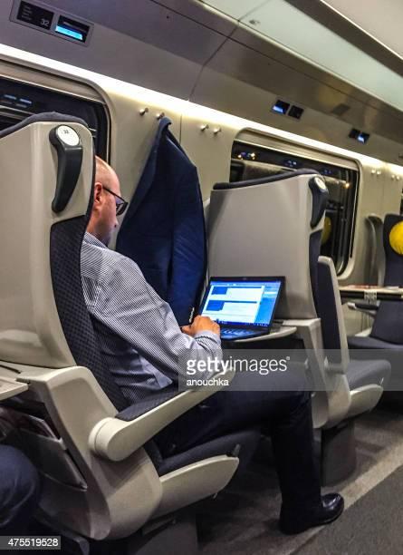 男性のラップトップで仕事する列車