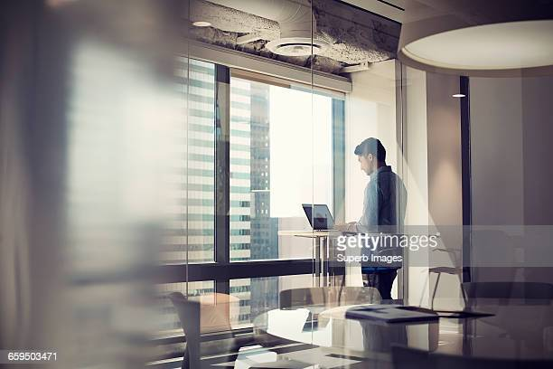 man working on laptop in business office - focus on background stock pictures, royalty-free photos & images