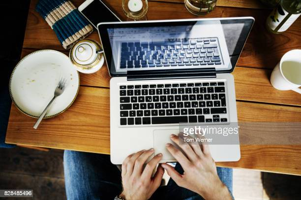 Man Working On Laptop In Cafe After Enjoying A Snack