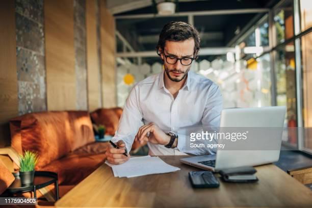 homem que trabalha no portátil no café - ver a hora - fotografias e filmes do acervo