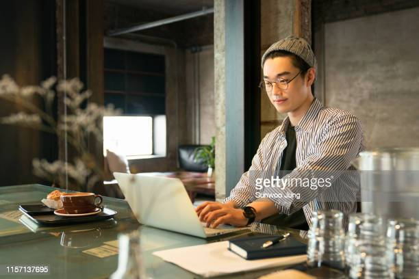 man working on laptop in modern cafe - korean ethnicity stock pictures, royalty-free photos & images