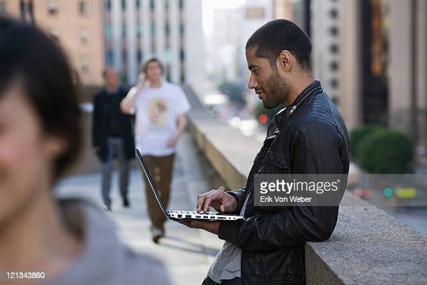 man working on laptop, people passing by - one mid adult man only stock pictures, royalty-free photos & images