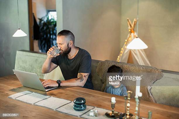 man working on laptop while sitting with son at dining table - home icon stock photos and pictures