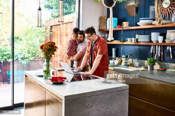 man working on laptop with husband and daughter in kitchen - weekend activities stock pictures, royalty-free photos & images
