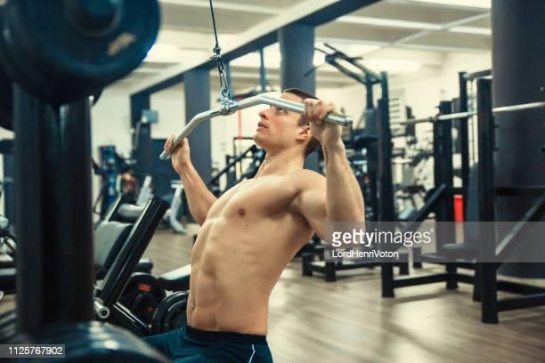 man working on lat machine - torace umano foto e immagini stock