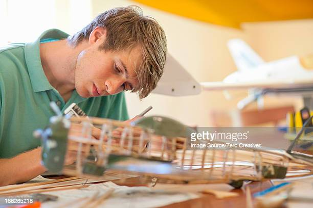 Man working on model airplane