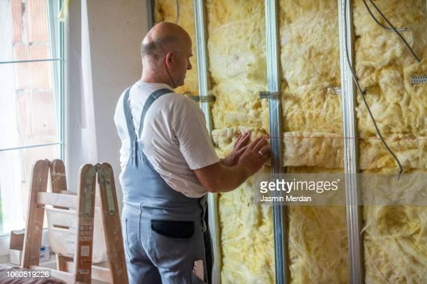 man working on rock wool of an home wall - wollig stockfoto's en -beelden