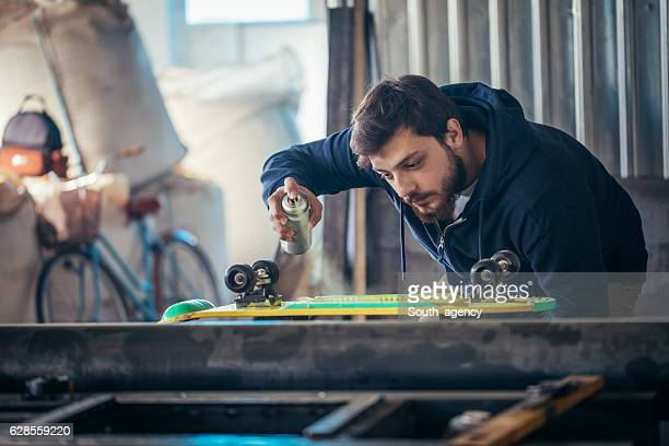 Man working on skateboard in a workshop