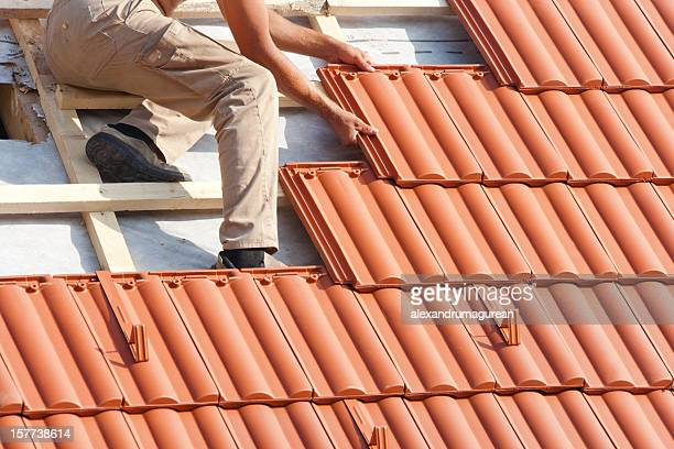 man working on the roof - roof tile stock pictures, royalty-free photos & images