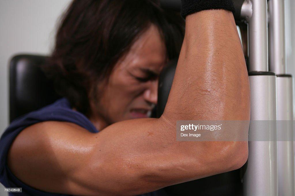 Man working on weight machine, close-up : Stock Photo