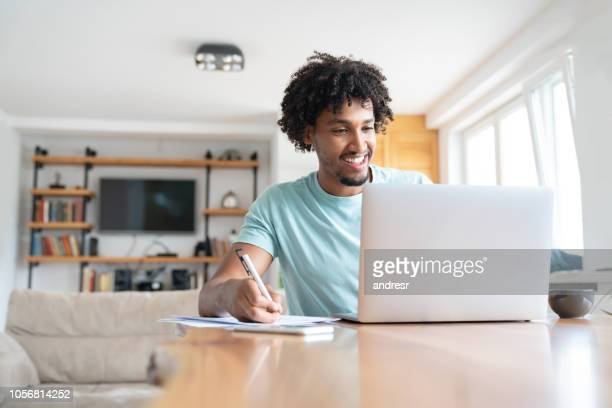 man working online at home - home finances stock pictures, royalty-free photos & images