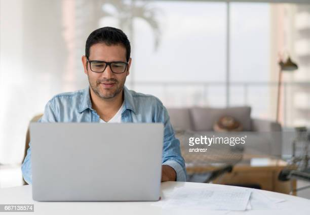 man working online at home - mid adult stock pictures, royalty-free photos & images