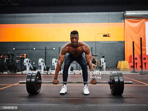 man working out in a gym with barbell and weights - weight training stock pictures, royalty-free photos & images